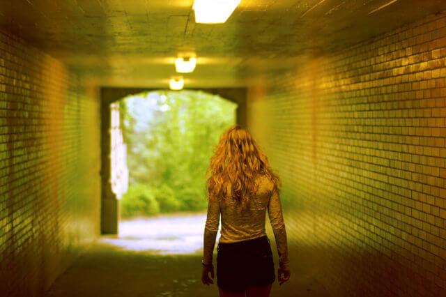 Girl walking through a tunnel